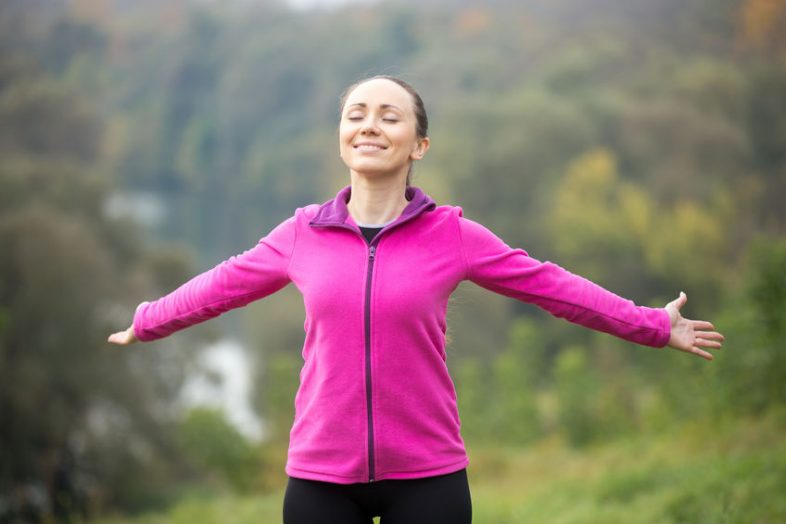63823563 - portrait of a smiling young woman outdoors in a sportswear, her hands outstretched, eyes closed. concept photo