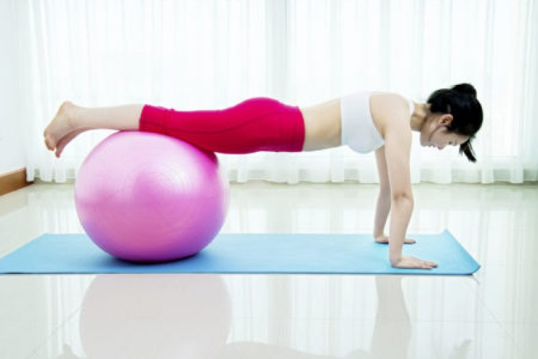 Asian young woman exercising on a fitness ball.